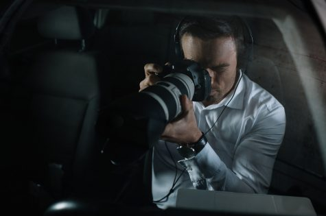 focused male private detective in headphones doing surveillance by camera from car